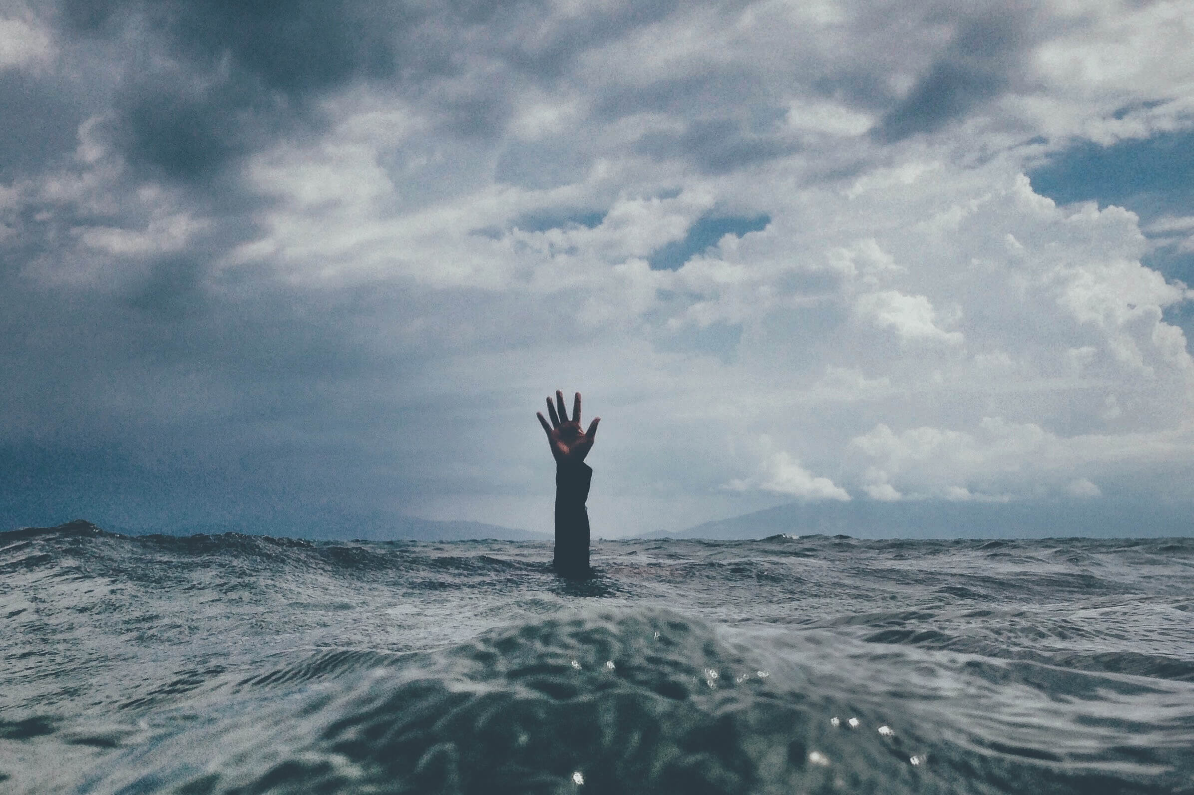 Person drowning in a sea of uncertainty and stress caused by an unsafe team environment