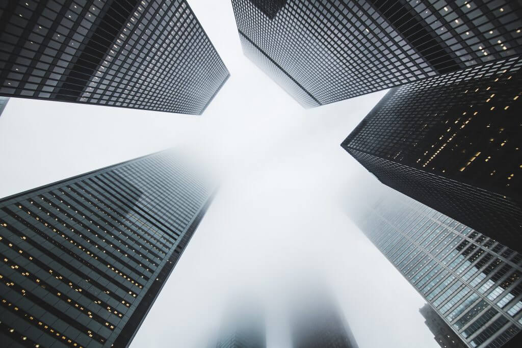 High rise buildings stretching up into a foggy sky to represent scaling Agile up and throughout an organization