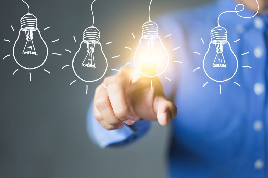 A man in a button down touches a lit light bulb, meant to convey the need for innovation in business during an age of rapid change and evolution in markets across the world.